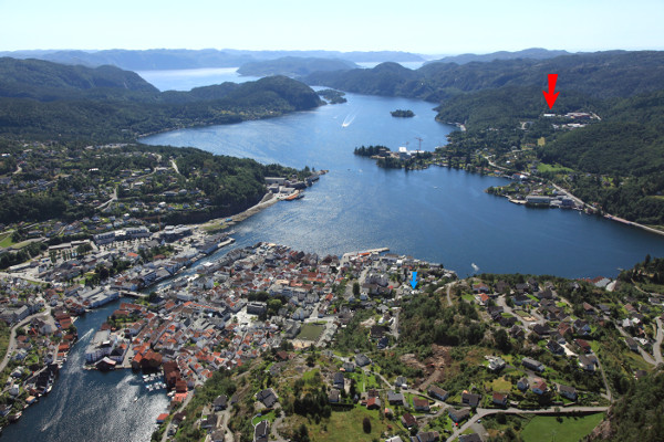 Overview of Flekkefjord with our factory shown with a red arrow as well as our previous location (blue arrow)